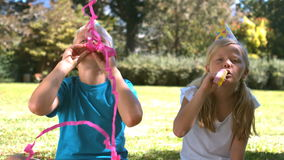Siblings with party hat having fun with party horn stock footage