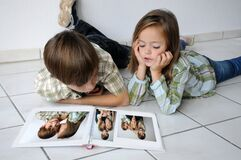 Siblings pass the time and look at photo albums