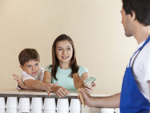 Siblings Paying For Chocolate Ice Cream To Waiter Royalty Free Stock Photography