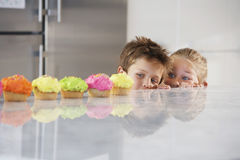 Siblings Peeking Over Counter At Row Of Cupcakes stock images