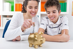 Siblings with piggybank Royalty Free Stock Photos