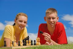 Siblings play chess. Together on sunny day Royalty Free Stock Photo