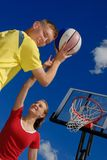 Siblings playing basketball. Teens playing basketball on sunny afternoon day Stock Image