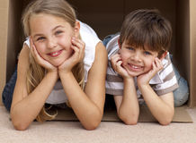 Siblings playing with boxes after moving house Royalty Free Stock Image