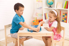 Siblings playing chess in the kid's room Royalty Free Stock Photos
