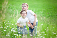 Siblings playing in field. Two cute young preschool siblings playing in green field or meadow Royalty Free Stock Photos