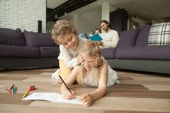 Siblings playing on floor while parents reading book on sofa. Happy siblings playing peek a boo or guess who drawing on warm wooden floor while parents reading Stock Photo