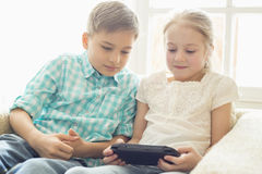 Siblings playing hand-held video game at home Royalty Free Stock Photo