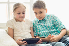 Siblings playing hand-held video game at home Stock Photography