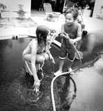 Siblings Playing With Hose and Water Stock Images
