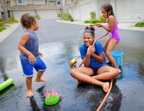 Siblings Playing With Hose and Water Royalty Free Stock Photos