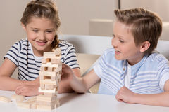 Siblings playing Jenga game at home together Royalty Free Stock Photos