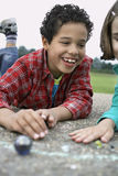 Siblings Playing Marbles On Playground Stock Photography