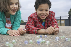 Siblings Playing Marbles On Playground royalty free stock photography
