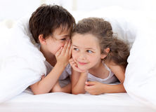 Siblings playing on parent's bed Stock Image