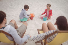Siblings playing by parents relaxing on launge chairs at beach Stock Photography