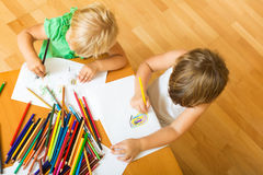Siblings playing with pencils Stock Photo