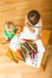 Siblings playing with pencils Royalty Free Stock Images
