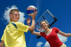 Siblings playing sport. Teens playing basketball on sunny afternoon day Stock Photos
