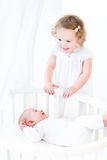 Siblings playing in sunny bedroom with round crib Royalty Free Stock Photo