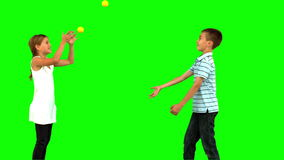 Siblings playing with tennis balls on green screen. In slow motion stock video footage