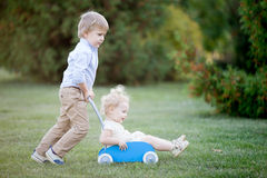 Siblings playing together. Portrait of two happy cute little siblings playing outdoors. Brother carrying his toddler sister in toy stroller, walking together in Royalty Free Stock Photography