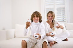 Siblings playing video game. Brother and sister playing video game together on white sofa, boy winning with girl frowning Stock Photo