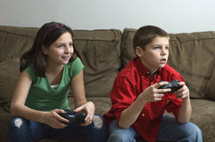 Siblings playing a video game Stock Photo