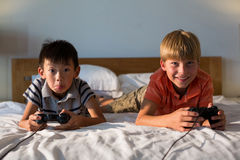 Siblings playing video game on bed Stock Photos