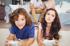 Siblings with playing video game on carpet. Close-up siblings with controlllers playing video game on carpet at home Royalty Free Stock Image