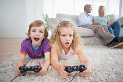 Siblings playing video game while parents sitting on sofa Royalty Free Stock Images