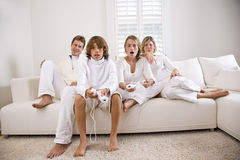 Siblings playing video game while parents watch Stock Photography