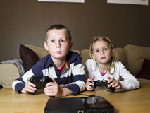 Siblings playing video games. Sitting in the sofa Stock Photo