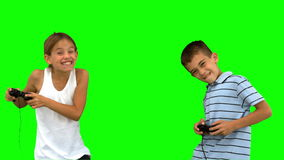 Siblings playing video games on green screen stock video