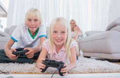 Siblings playing video games. In the living room royalty free stock photography