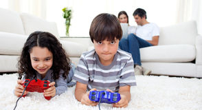 Siblings playing video games lying on the floor. With their parents in the background Stock Photo
