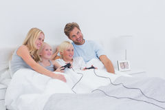 Siblings playing video games with parents watching Royalty Free Stock Image