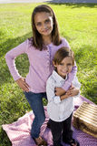 Siblings posing for camera having picnic in park Royalty Free Stock Image