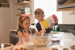 Siblings preparing food in kitchen royalty free stock photography