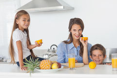 Siblings raising a half orange in the kitchen Royalty Free Stock Photo