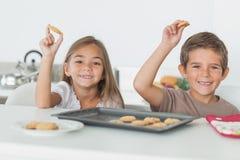 Siblings raising homemade cookies Stock Photo