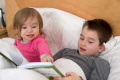 Siblings Reading. Little sister pointing a page to his older brother in the book before they go to sleep Royalty Free Stock Image