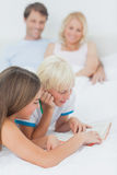 Siblings reading a book on the bed Stock Photography
