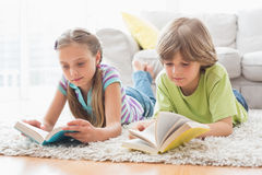 Siblings reading books while lying on rug Stock Image