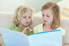 Siblings reading magazine on the couch Stock Image
