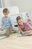 Siblings reading story books on floor in the living room Royalty Free Stock Photos