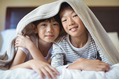 Siblings relaxing under blanket in bedroom Royalty Free Stock Image