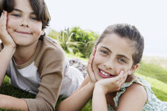 Siblings Resting Chin In Hands While Lying On Grass royalty free stock image