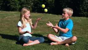 Siblings sat in a park playing with tennis balls. In slow motion stock footage