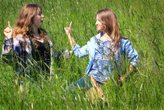 Siblings Serious Discussion. Two pretty country teen girls with long brown hair, standing in tall grass having a friendly serious discussion with each other Stock Photography